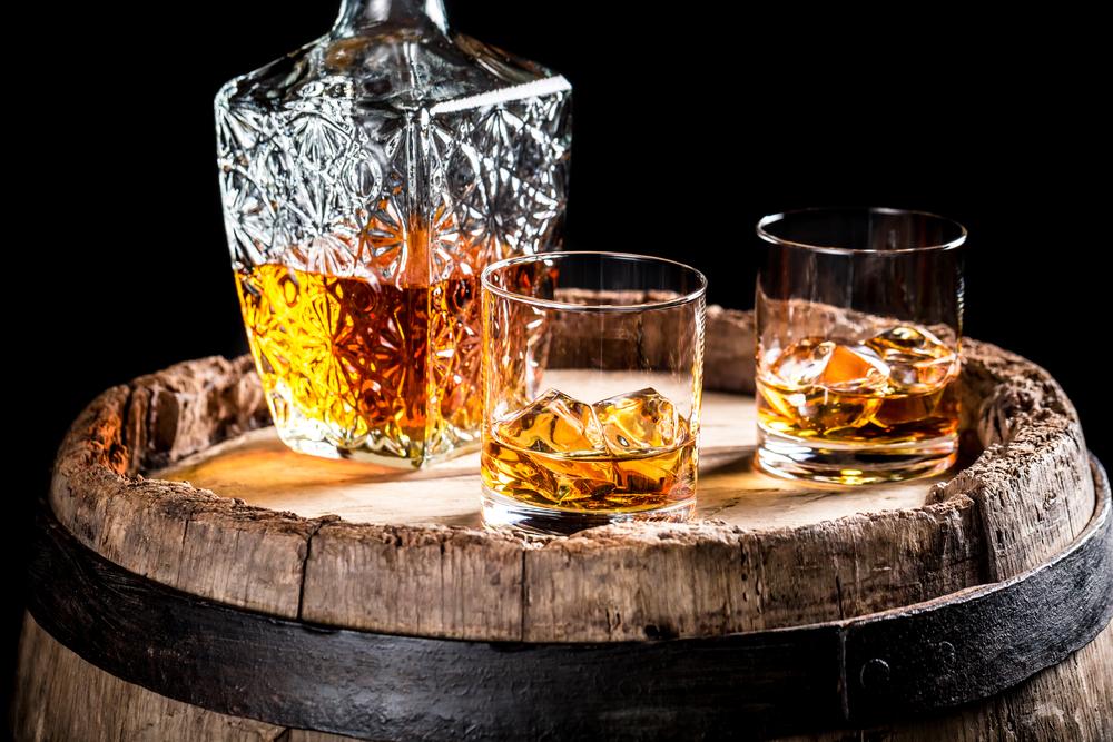 En bägare och två glas fyllda med whiskey ovanpå en rustik tunna