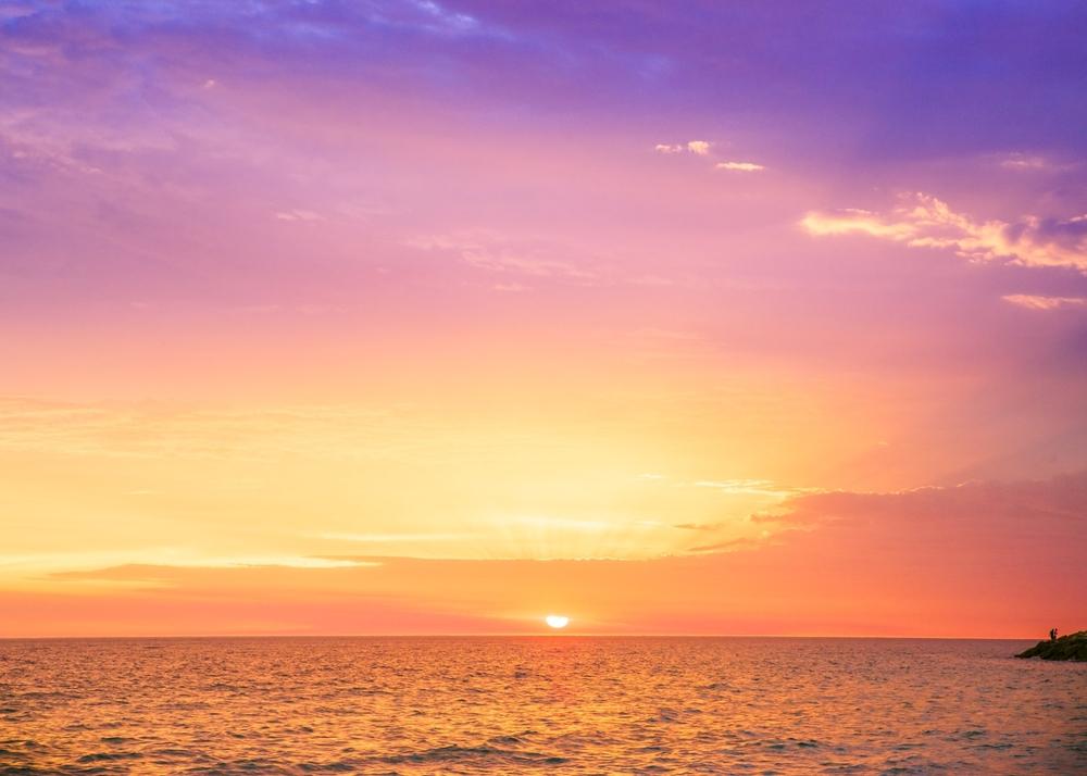 Solnedgång över strand.