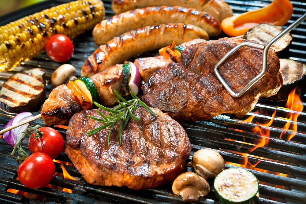 Kött, majs, svamp och grönsaker på grillen.