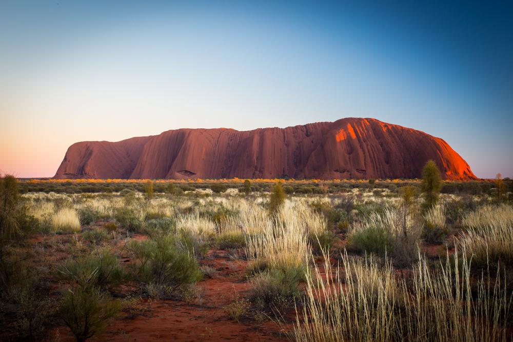 Ayer's Rock, också kallad Uluru. En enorm bergskulle på slätten som färgas röd av solnedgången.